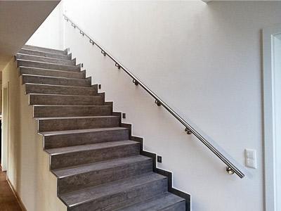 Edelstahl Handlauf gerade für Innentreppe an einer Wand aus Hochlochziegeln montiert