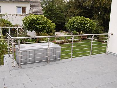Terrassengeländer aus Edelstahl gebogen ion aufgesetzter Montage mit Querstreben aus Rd14 mit Stabhaltern vor den Pfosten montiert