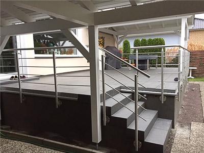 Terrassengeländer in seitlicher Montage mit einer Füllung aus Edelstahlseil, angrenzendes Geländer für Treppe mit einer Füllung aus Rundmaterial