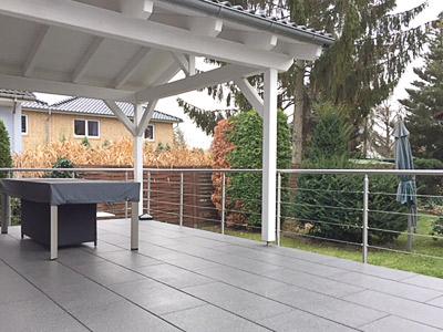 Terrassengeländer in seitlicher Montage mit einer Füllung aus Edelstahlseil - Ansicht von der Terrasse aus, mit Blick auf das Seilgeländer