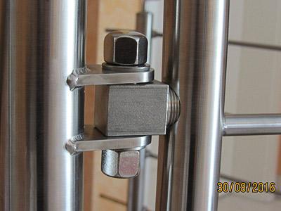 Schutztür aus Edelstahl an einer Innentreppe, Detail mit Türband