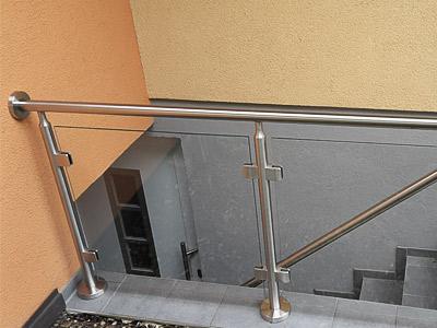 Treppengeländer für Brüstung an Kellertreppe mit einer großflächigen Glasfüllung, Geländerhandlauf mit Übergang in Treppenhandlauf mit Wandbefestigung - Ansicht von der Seite