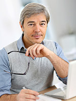 Mann am Laptop bei der Planung eines Balkongeländers