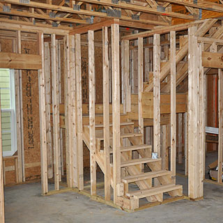 Holzständerwände im Rohbau - für einen Handlauf an der Trockenbauwand müssen jetzt die Maße notiert werden
