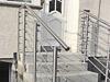 beidseitige Geländer aus Edelstahl mit 6 Querstreben - Montage mit Wangenplatten an den Stufen - Blickauf die Treppe
