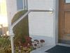 Montage des Geländerbügels durch Einbetonieren und Verschrauben an der Hauswand