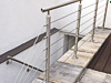 Geländer aus Edelstahl mit 6 Seilen an Kellerabgang - Pfosten in aufgesetzter Montage, zusätzliche Wandbefestigung des Handlaufes