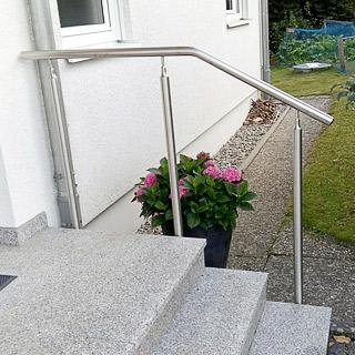 Eingangstreppe mit breitem Podest und einem freistehenden Handlauf mt 3 Unterstützungspfosten in seitlicher Montage